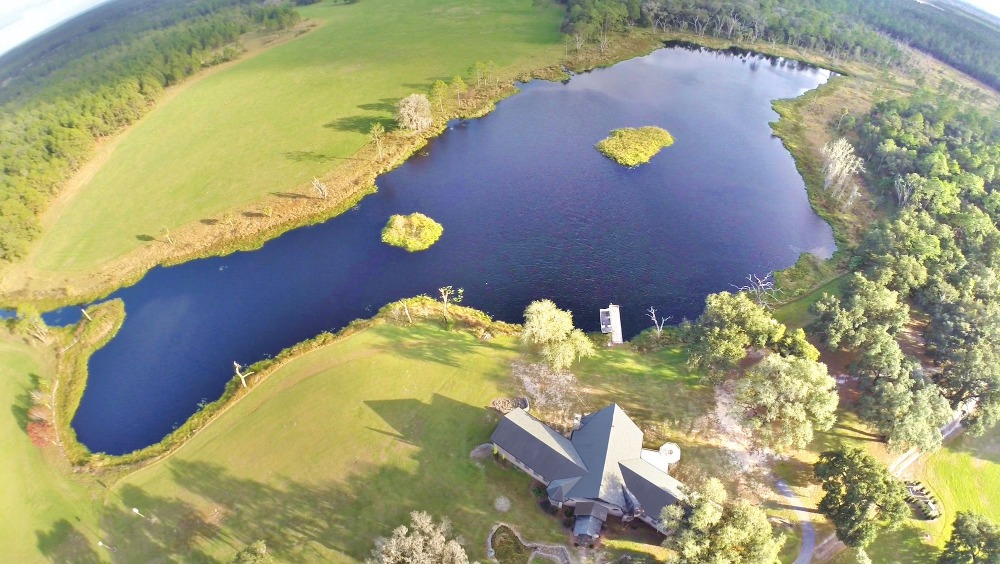 A much brighter aerial view of the property showcasing the gorgeous natural landscape surrounding the house. Images courtesy of Toptenrealestatedeals.com.