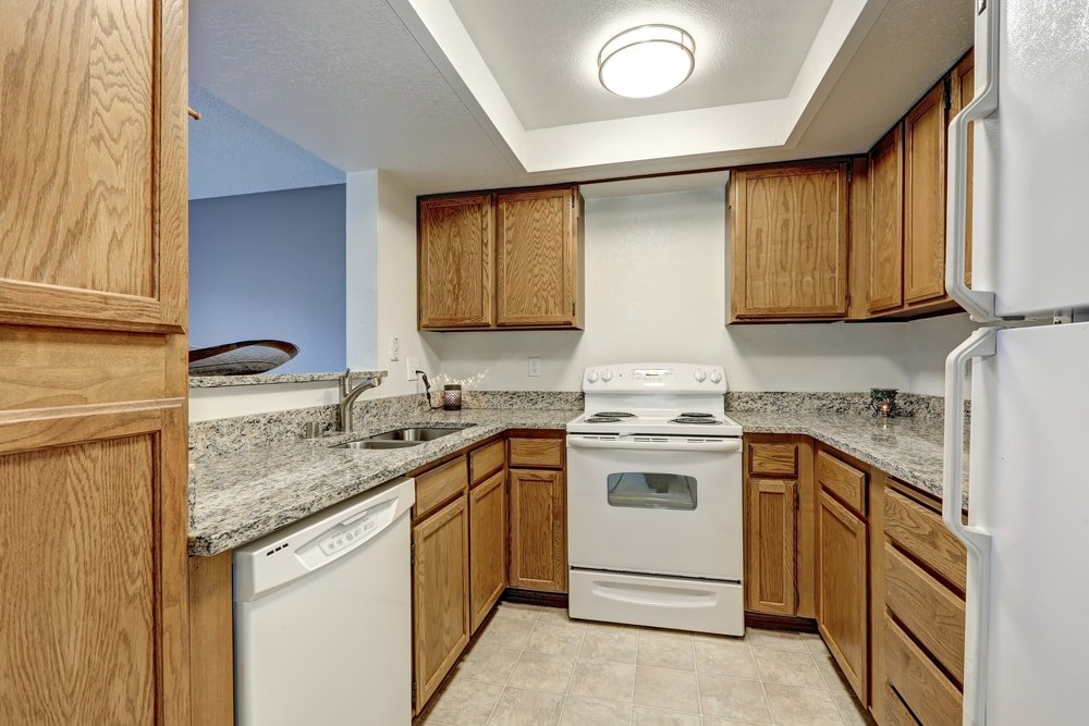 Small U-shaped kitchen with wood cabinetry and white appliances.
