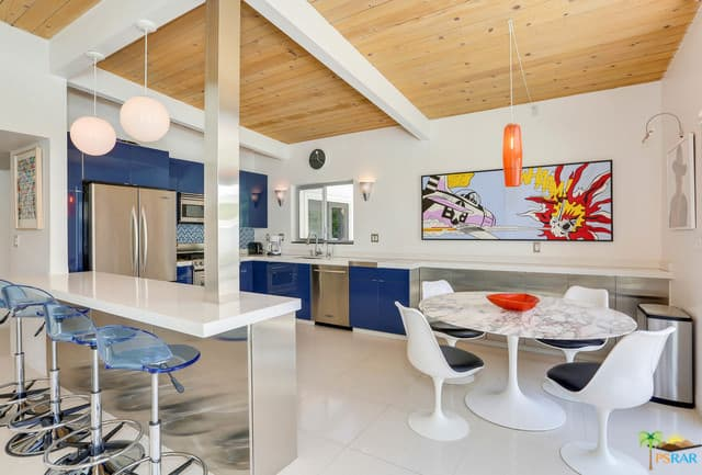 This is a lovely kitchen with with a peninsula on the side connected to the white exposed beams of the wooden ceiling with a stainless steel column at the edge. On the other end of this peninsula is another white column connected to the white beams of the ceiling and the white countertop of the peninsula.