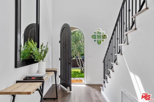 The beautiful arched main door of this foyer has a black tone that pairs well with the black console table, mirror and the wrought-iron railings of the staircase that stands out against the white walls adorned with a lovely flower-shaped window on the side.