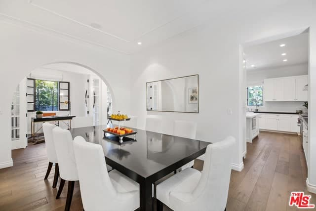The highlight of this simple and elegant dining room is the large black rectangular dining table that stands out against the white slipcovers of the chairs, the walls and the white ceiling with recessed lights.