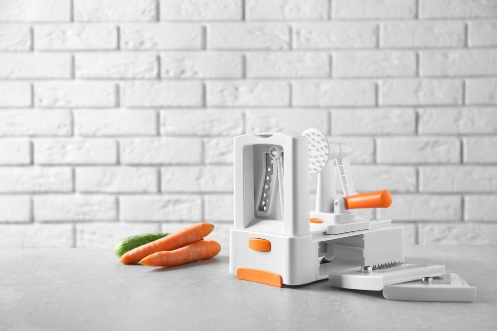 Spiral vegetable slicer and carrots on a table.