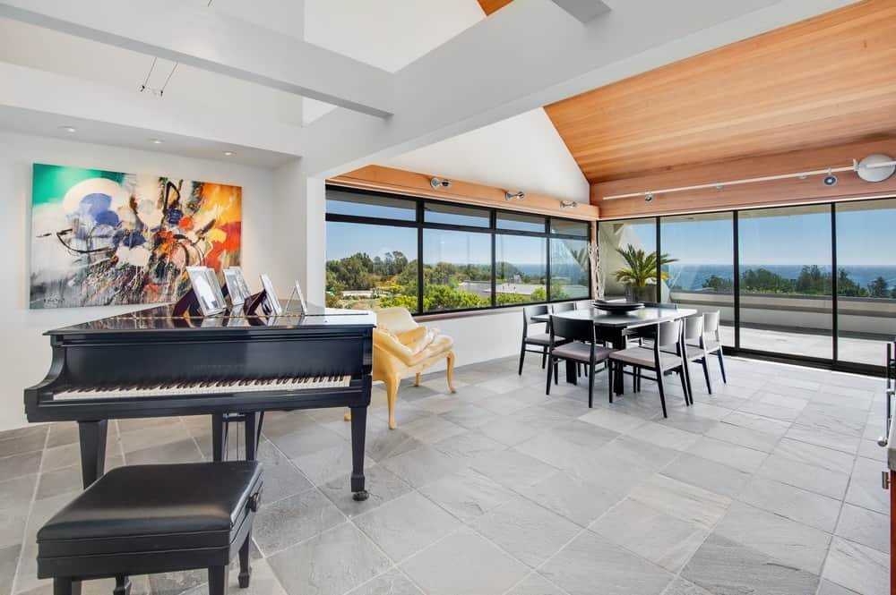 This is the dining area placed in a bright corner adorned by the beautiful views of the glass windows and glass doors. The black dining set matches well with the grand piano on the other side of the room making them stand out against the white walls.