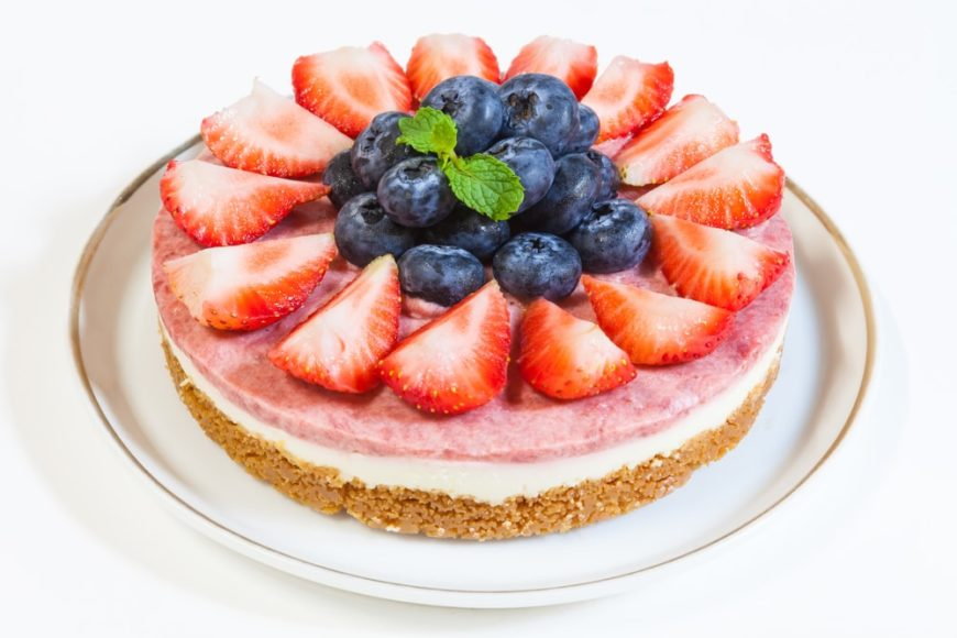 Mixed berries cream cheese cake on a white platter.