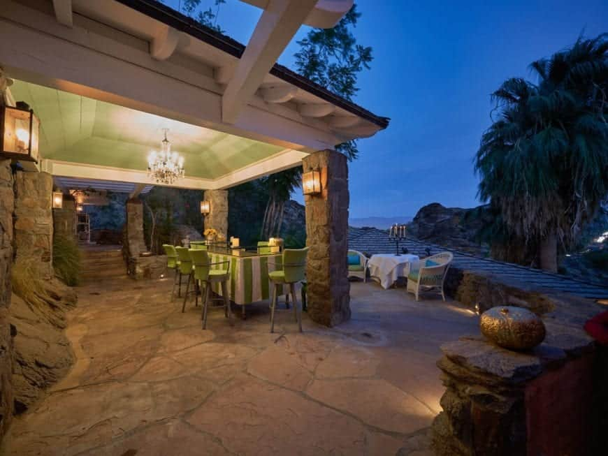 This is a look at the beautiful covered patio fitted with an outdoor dining set standing on a mosaic stone flooring bordered with decorative rocks and stone walkways.