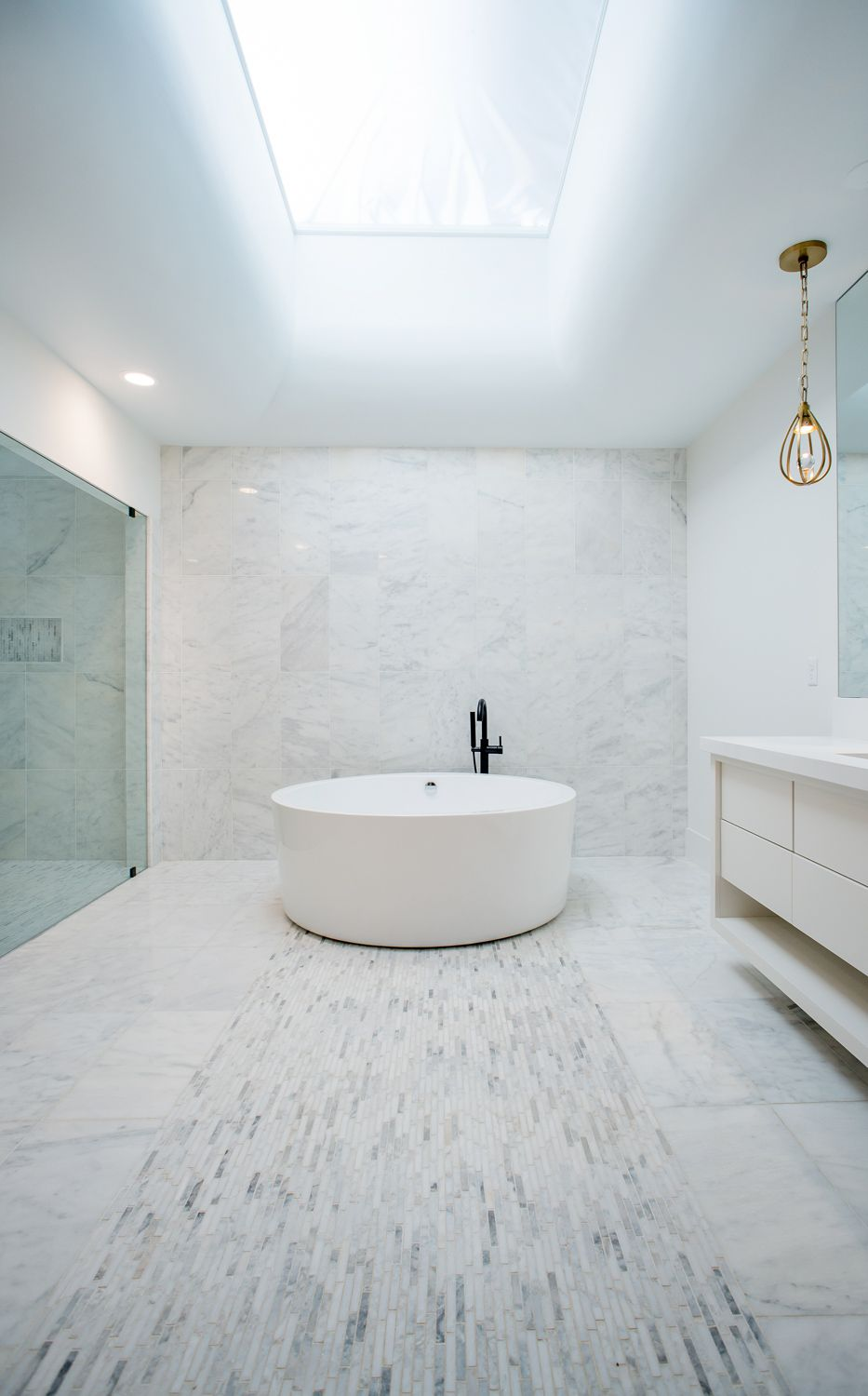 This bathroom has a round freestanding bathtub on the far side standing in the middle of the floor between the glass-enclosed shower area and the vanity. Images courtesy of Toptenrealestatedeals.com.