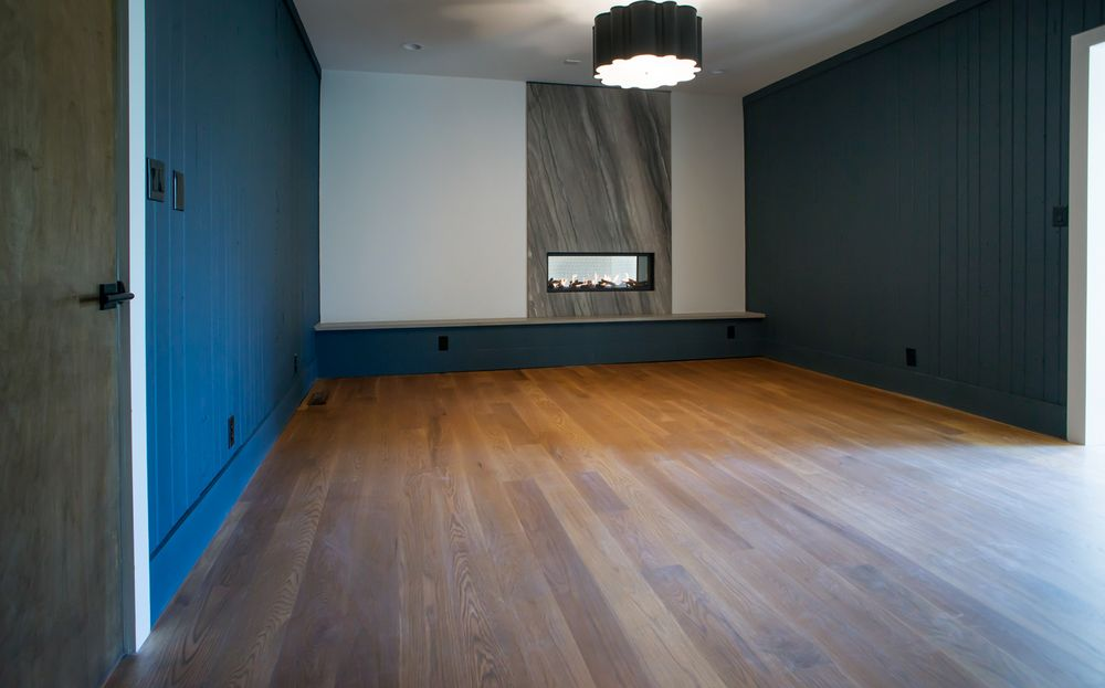 This spacious bedroom has gorgeous navy blue walls that complement the hardwood flooring. On the far wall, it has a modern fireplace housed in a gray wall panel. Images courtesy of Toptenrealestatedeals.com.