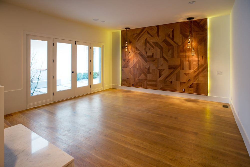 This spacious bedroom has a lovely wall that has unique wooden designs that would be perfect for the headboard of a bed. Beside this is a row of glass doors that brighten the beige walls and hardwood flooring. Images courtesy of Toptenrealestatedeals.com.