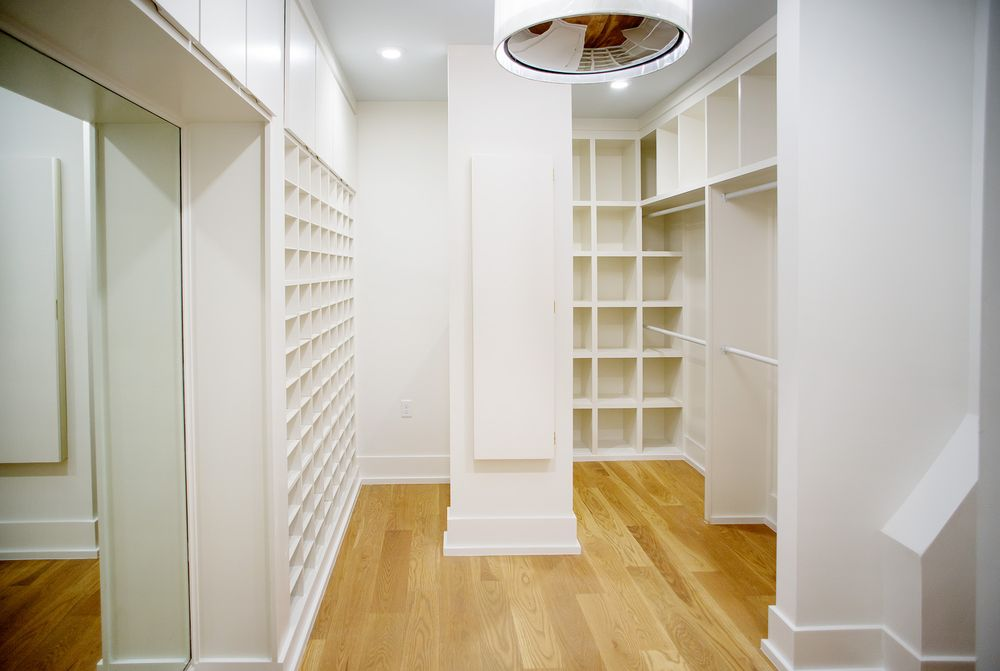 This is the spacious and bright walk-in closet with built-in white wooden structures on the walls for storage that is complemented by the hardwood flooring. Images courtesy of Toptenrealestatedeals.com.