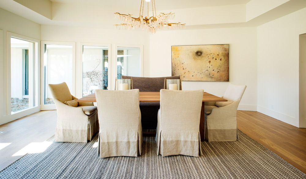 This is the dining room with a large wooden rectangular dining table surrounded by chairs with beige slipcovers to match the walls. These are then topped with a decorative chandelier. Images courtesy of Toptenrealestatedeals.com.