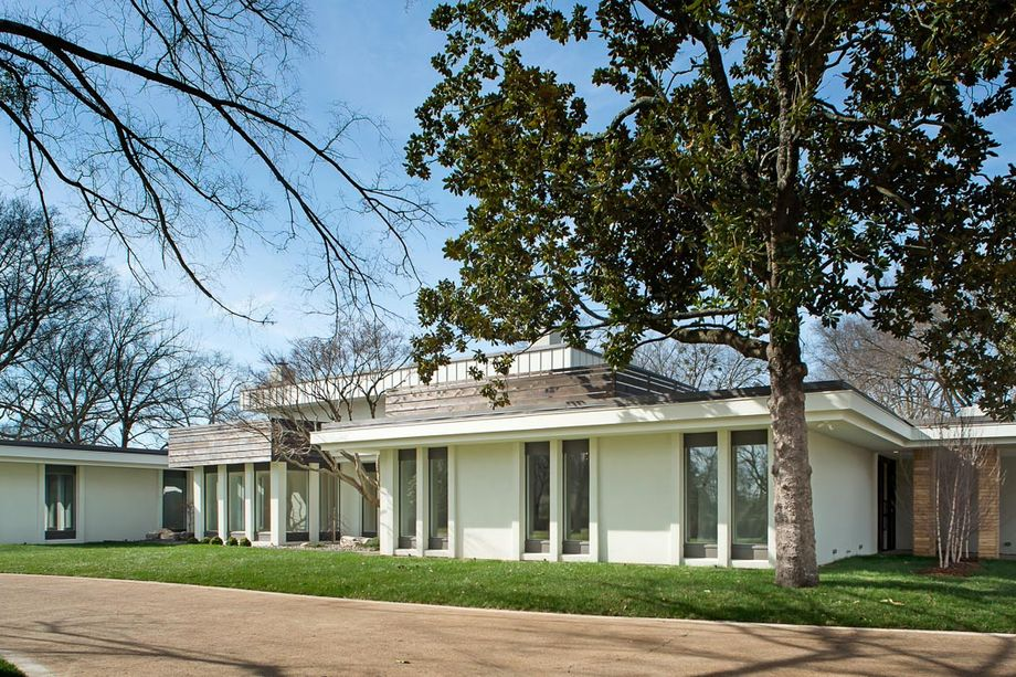 This is the gorgeous front view of the house that has beige exterior walls and tall thin glass windows. These are then adorned with grass lawns and tall trees. Images courtesy of Toptenrealestatedeals.com.