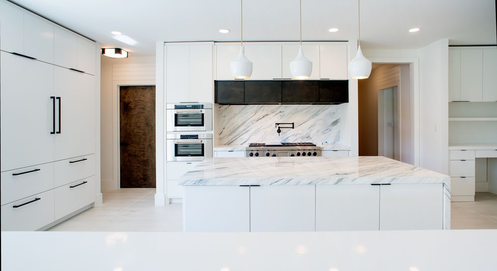 This view of the kitchen shows more of the modern stainless steel appliances that stand out against the consistent white marble tones of the kitchen island and backsplash. Images courtesy of Toptenrealestatedeals.com.