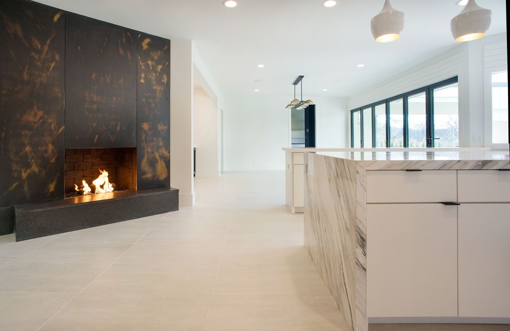 This is a closer look at the bright and white kitchen. Here you can see the dark marble fireplace of the kitchen. It stands out against the light tones of the rest of the kitchen. Images courtesy of Toptenrealestatedeals.com.