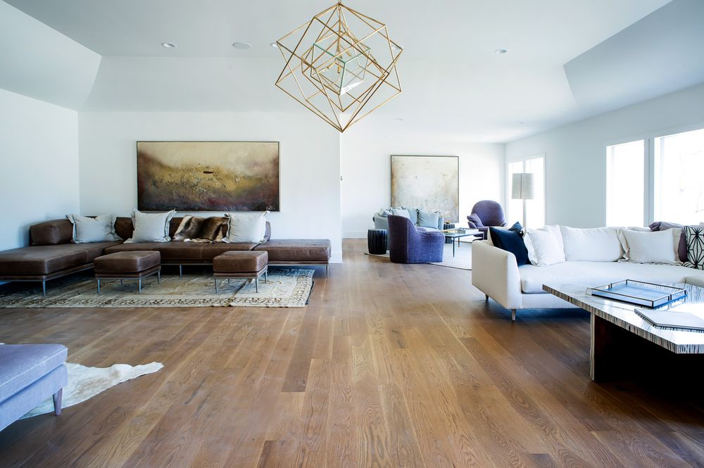 This great room has enough space for multiple living room areas and lounge areas with enough remaining hardwood flooring for an open middle area under the decorative geometric lighting. Images courtesy of Toptenrealestatedeals.com.