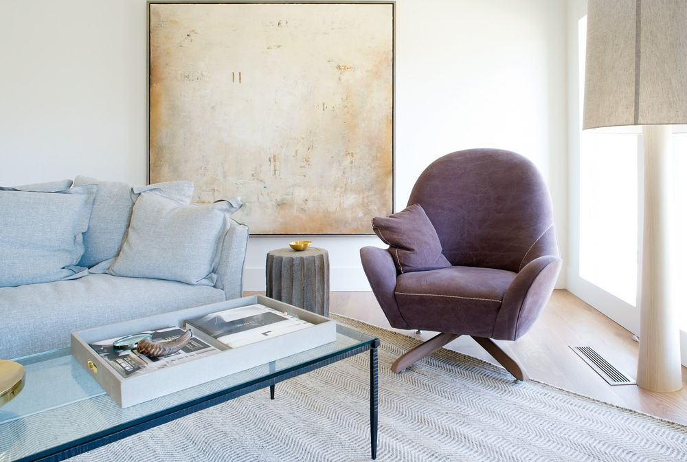 This is a closer look at the corner of the living room that has a comfortable cushioned armchair illuminated by the tall glass window and adorned with a large wall-mounted artwork. Images courtesy of Toptenrealestatedeals.com.