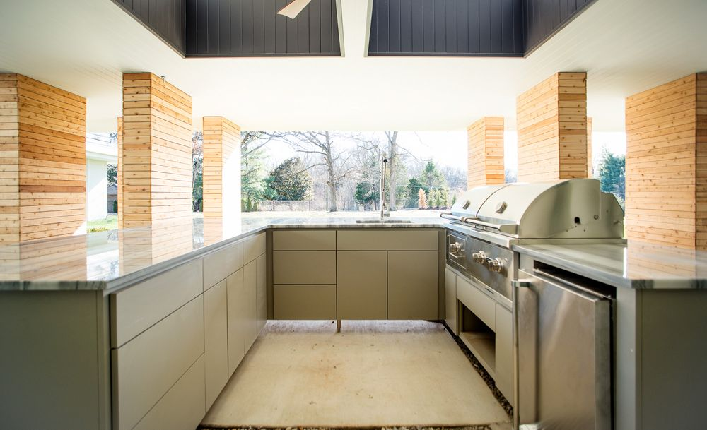 This is the U-shaped outdoor kitchen with a lovely ceiling supported by beige pillars. The light gray cabinetry pairs well with the stainless steel appliances and grilling station. Images courtesy of Toptenrealestatedeals.com.