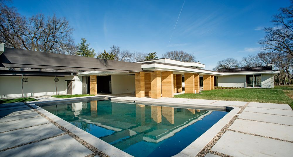 The back of the house has a lovely pool that is surrounded by the lush landscaping of grass lawns and charming beige pillars. Images courtesy of Toptenrealestatedeals.com.