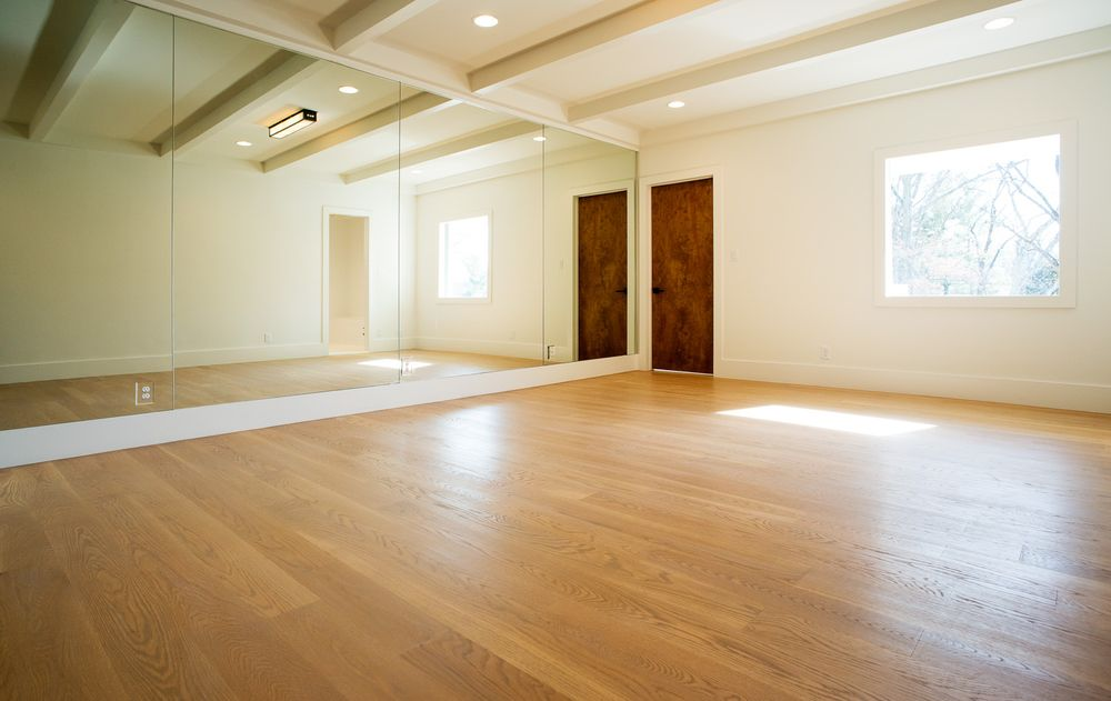 This is the beautiful dance studio of the house with a spacious hardwood flooring paired iwth beige walls, beige ceiling with exposed beams and a wide wall of seamless mirror. Images courtesy of Toptenrealestatedeals.com.