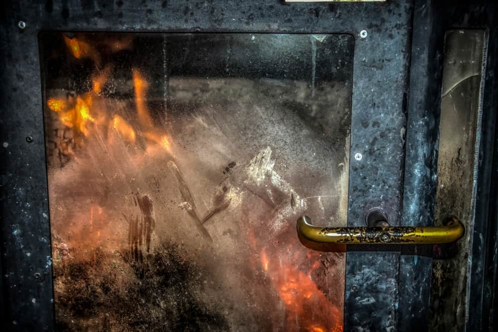 A close-up of a burning furnace with a glass cover dirtied with soot.