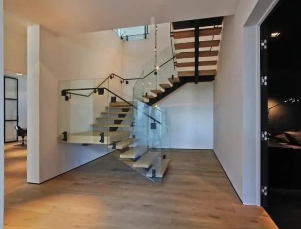 This is a simple and spacious foyer with a wide hardwood flooring that complements the white walls and ceiling. These make the black accents of the modern staircase stand out along with the pitch black main doors.