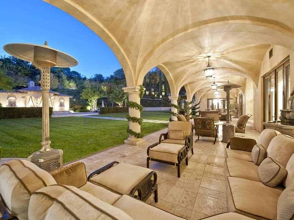 This is a large patio with sitting areas underneath a row of groin vault ceiling with pillars that match well with the beige flooring tiles. These stop at the edge of the grass lawn that leads to the backyard.