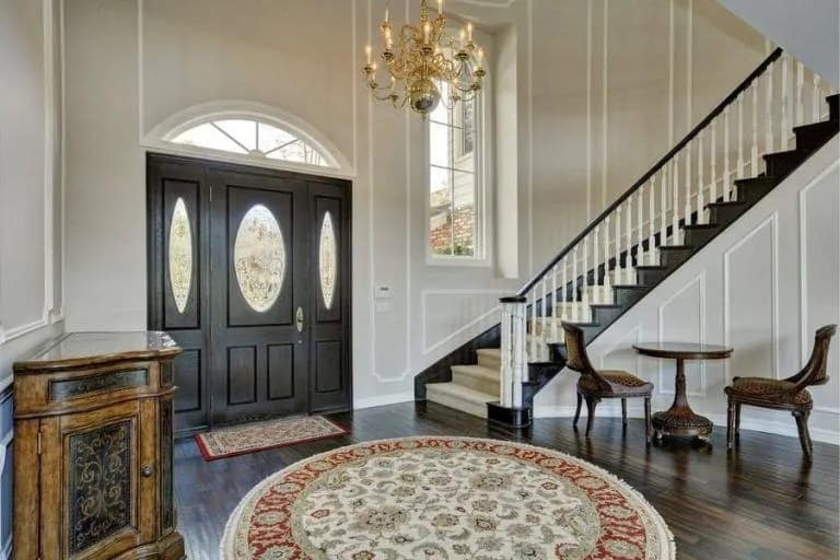 This is a luxurious and welcoming foyer with a black wooden main door that pairs well with the hardwood flooring and the staircase on the side. These stand out against the white walls and the white patterned area rug by the door.