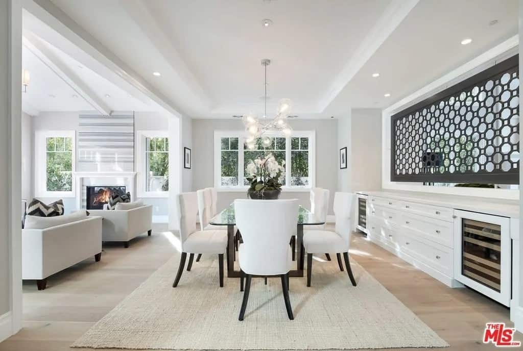The formal dining room has bright white walls with a built-in white cabinetry to match the white tray ceiling and white chairs surrounding the glass-top dining table. These make the black decorative screen and the legs of the chairs stand out.