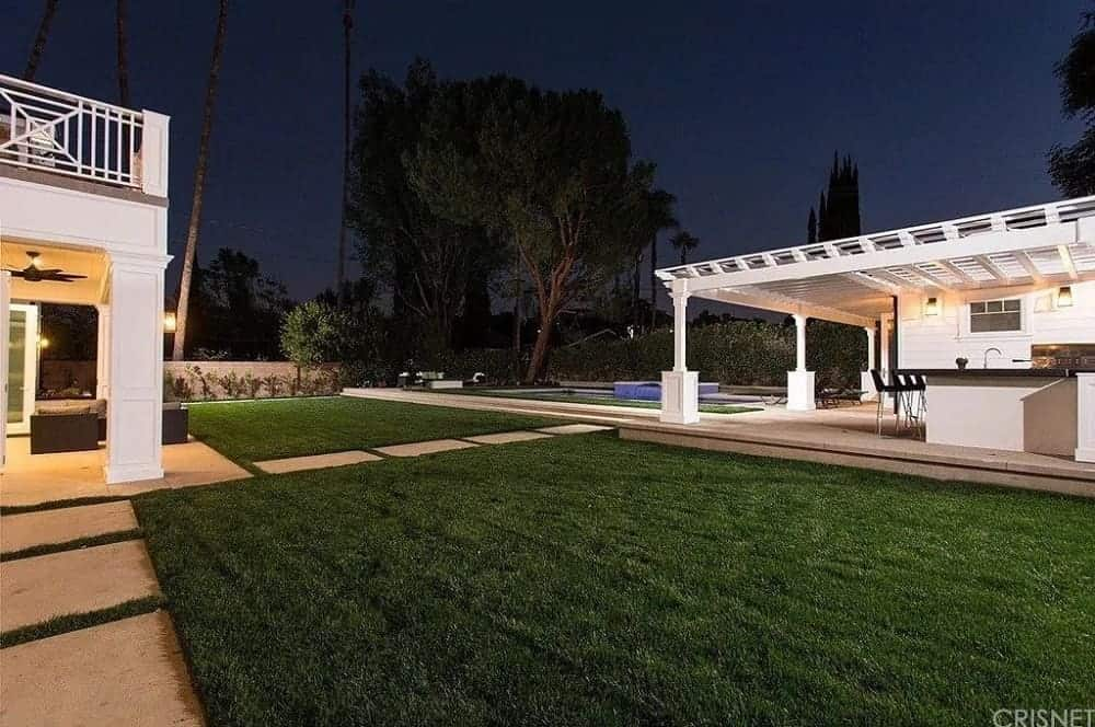 This is a gorgeous view of the backyard showcasing a covered patio right outside the house. It has a comfortable sofa set on a concrete flooring that connects with the concrete slab walkways of the grass lawn.