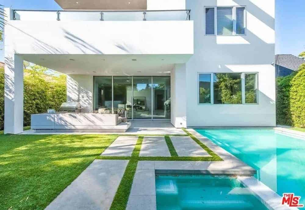 This is a lovely view of the backyard patio from the poolside area. Here you can see the comfortable outdoor sofa of the patio fitted on a concrete floor that transitions to concrete walkways surrounding the pool beside the grass lawn.