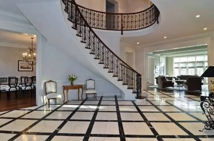This is a grand patio with a black white marble flooring with checkered patterns. This matches well with the white walls, white ceiling and the black intricate wrought-iron railings of the curved staircase.