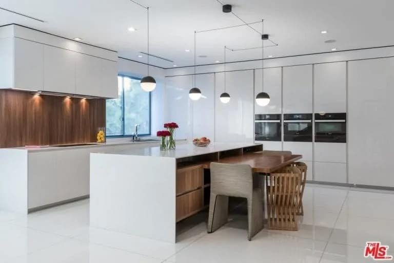 This view of the bright and white kitchen showcases the large white waterfall kitchen island that has a built-in wooden table beside it paired with various chairs. This is topped with a pendant light hanging from the white ceiling.