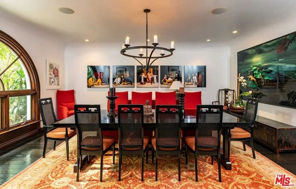This gorgeous formal dining room has a large black dining table paired with black chairs and a black round chandelier that stands out against the white ceiling and walls adorned with artworks and a large arched window.