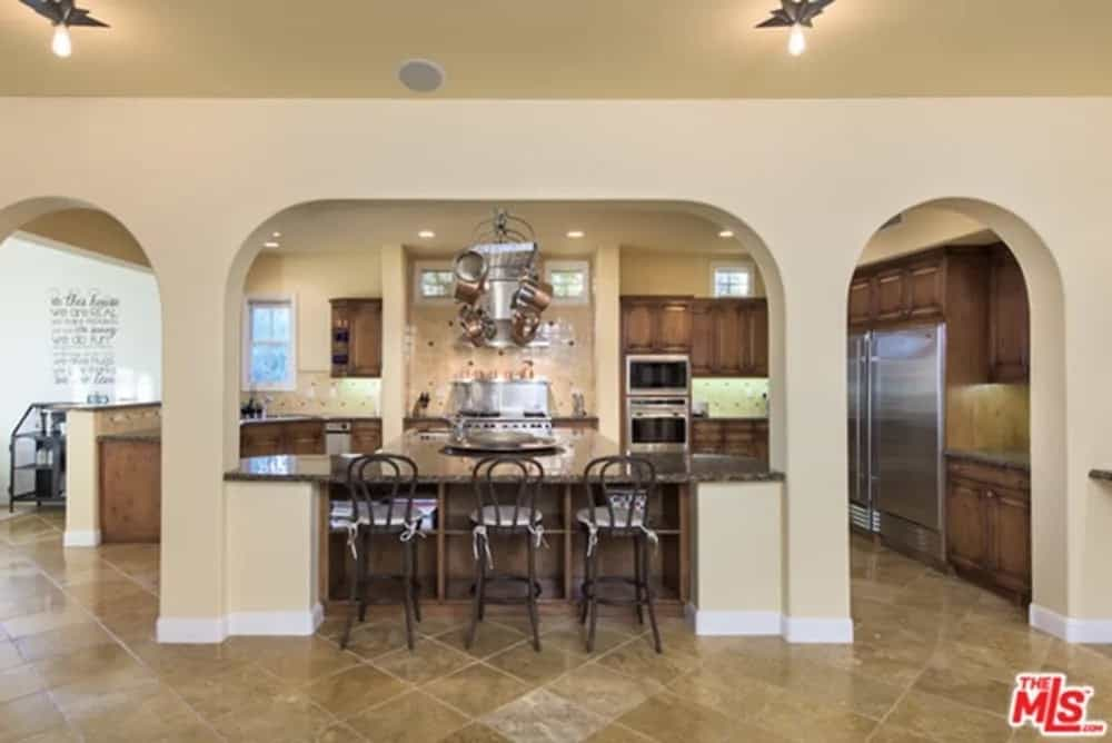 This view of the kitchen showcases the dark countertop of the breakfast bar. This is complemented by the lovely beige arches and columns that blend well with the beige ceiling.