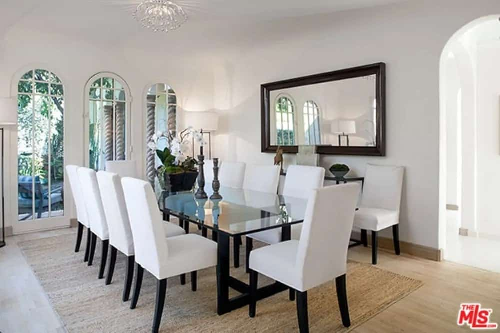 This elegant formal dining room has a large glass-top dining table with black legs to match those of the white chairs surrounding the table. These black details pair well with the frames of the wall-mounted mirror that stands out against the white wall.