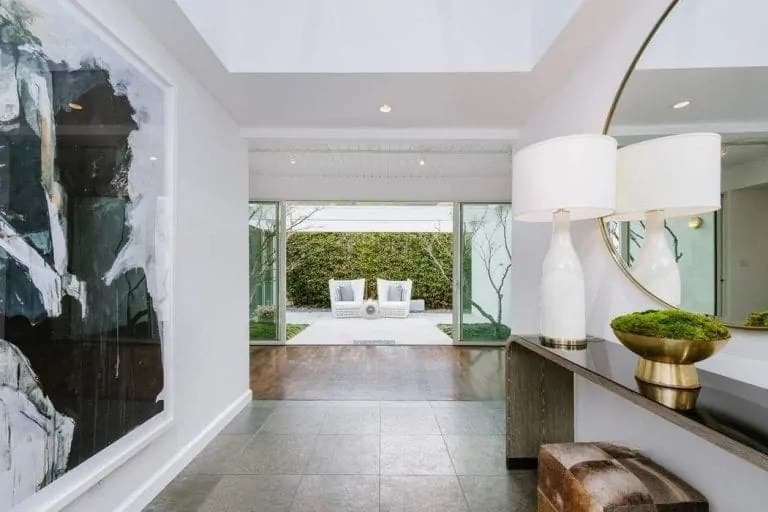 Upon entry, you are welcomed by this elegant and simple foyer with dark flooring tiles to match the black console table on the side across from the black and white wall-mounted artwork. These stand out against the white walls and ceiling.