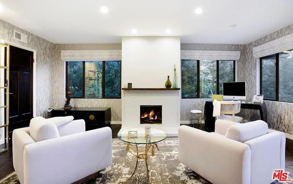 This is a gorgeous home office with a bright white ceiling, white fireplace and a couple of white cushioned armchairs. These are contrasted by the dark flooring, black cabinet and the black modern desk at the corner by the windows.