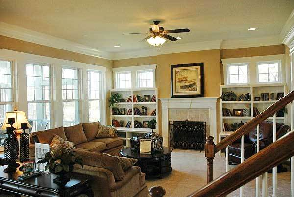 The family room has beige sectionals, a round coffee table, leather armchair, and a marble fireplace flanked by white built-ins.