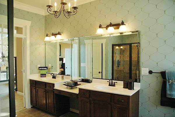 A closer view of the dual sink vanity shows the wrought iron fixtures and chrome framed mirror lit by two sets of glass sconces.