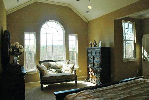 The sitting area is furnished with a dark wood dresser, a vanity, and a comfy seat situated against the arched window.