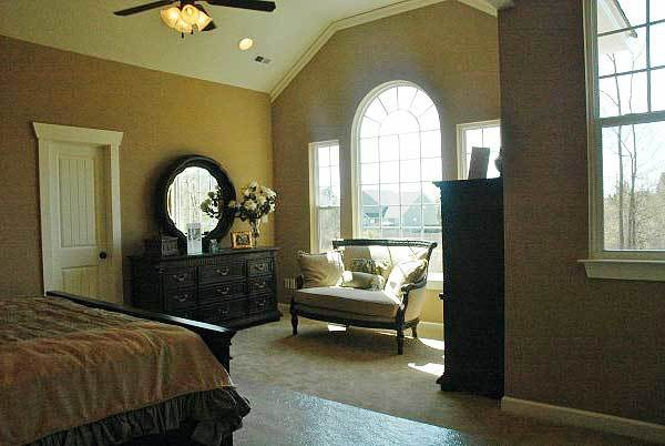 Primary bedroom with beige carpet flooring and a vaulted ceiling mounted with recessed lights and a fan.