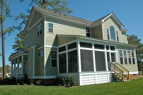 Angled rear exterior view showing the taupe siding and the screened porch complemented with a wooden staircase.