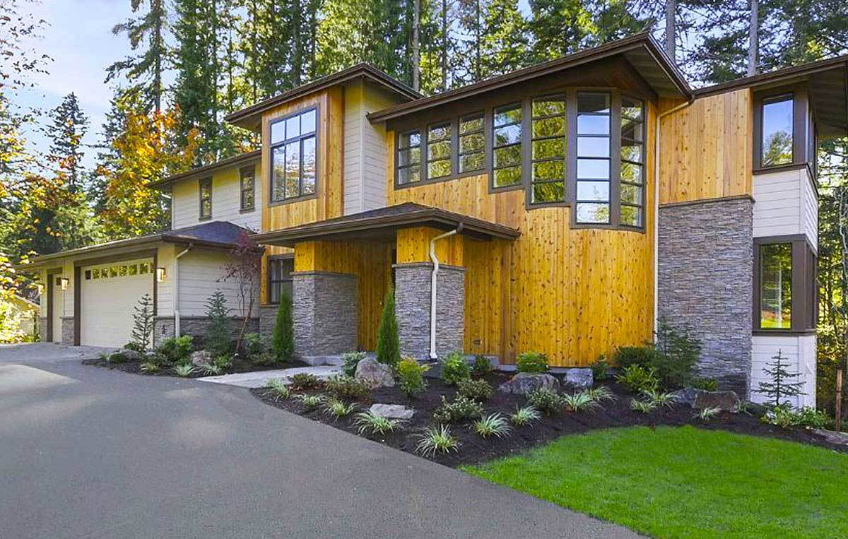 Home facade with wood-paneled siding, hipped roofs, and gorgeous stone accents.