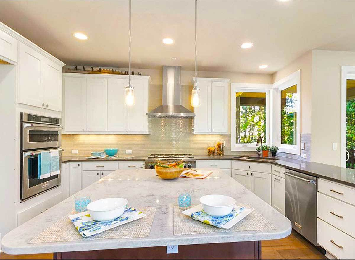 A closer look at the kitchen island with marble countertop lit by glass pendant lights.