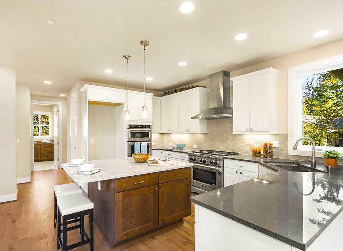 The kitchen is equipped with stainless steel appliances, white cabinets, and an immense center island.