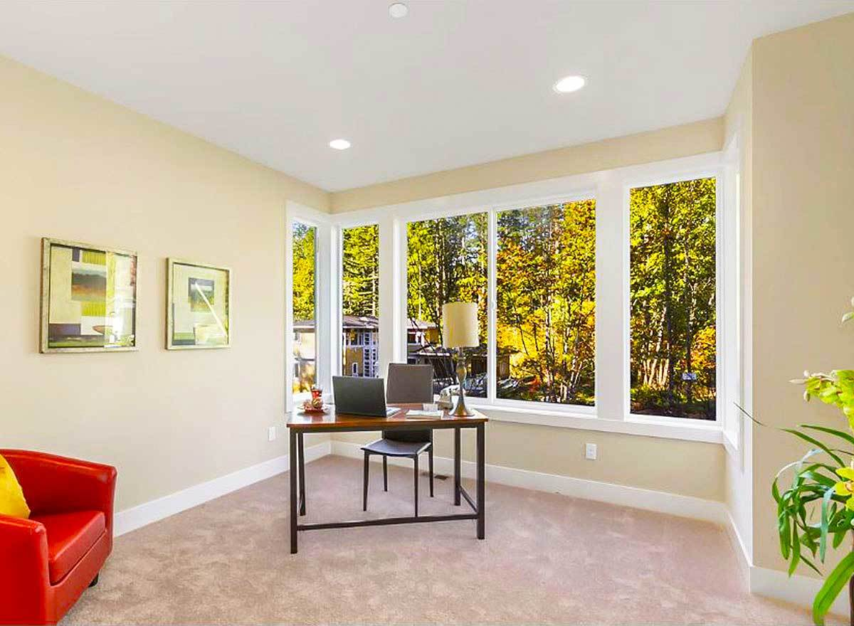 The study has carpet flooring, glass-paneled windows, and beige walls adorned with framed artworks.