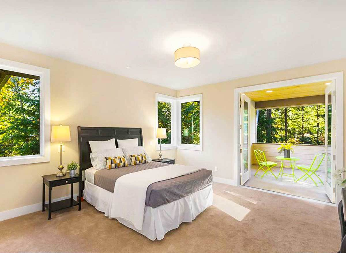 The primary bedroom offers dark wood furnishings and a french door that leads out to the private balcony.
