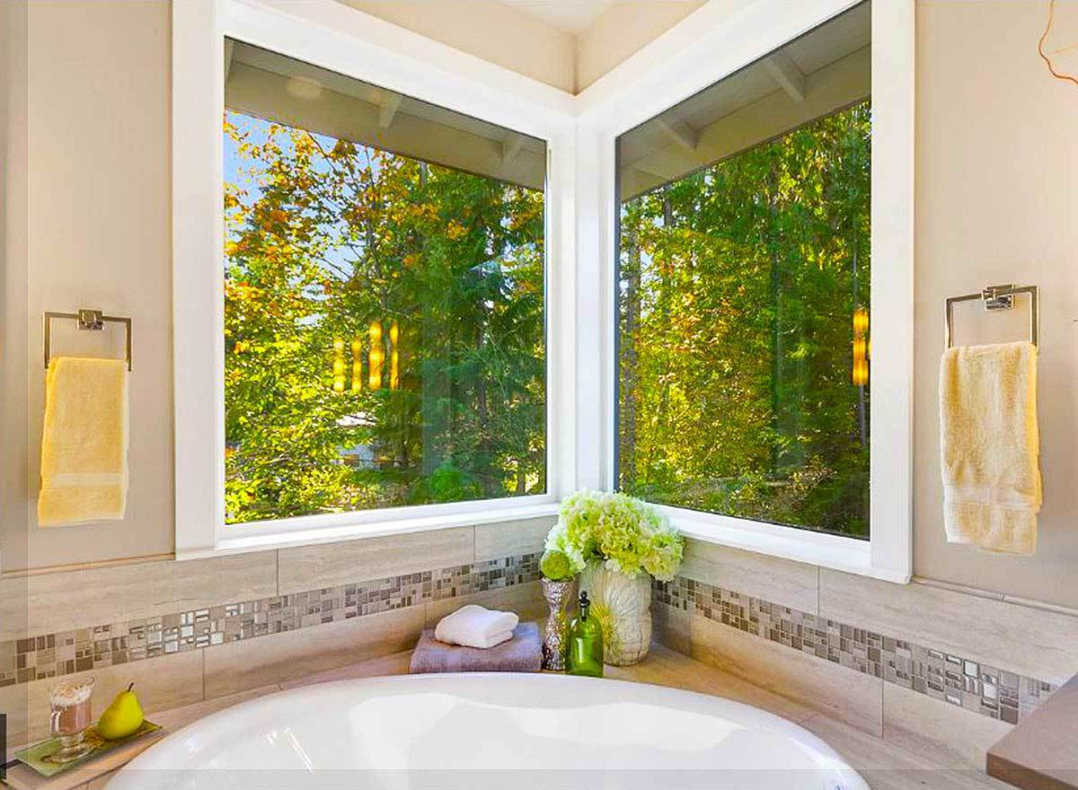 Picture windows sit above the corner tub. It is flanked with brass towel racks mounted against the beige walls.