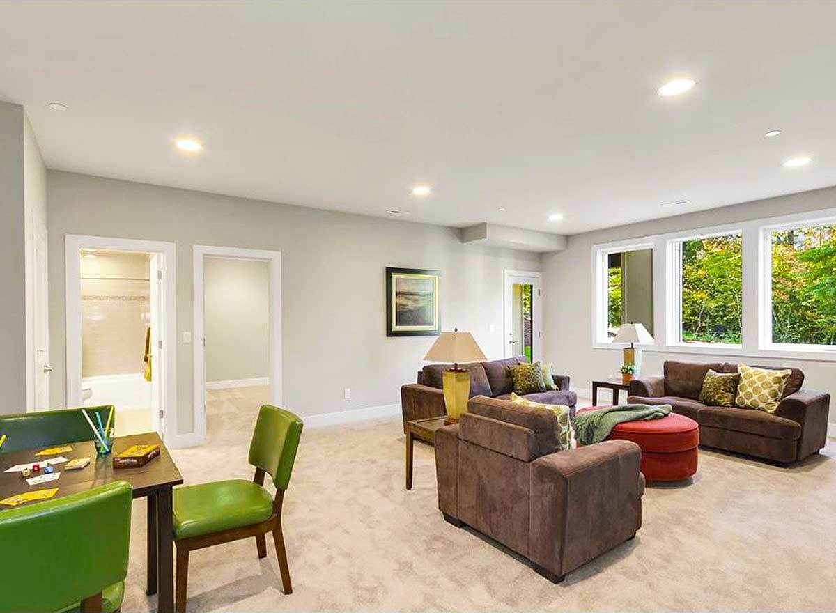 The recreation room includes beige carpet flooring and its own bathroom.