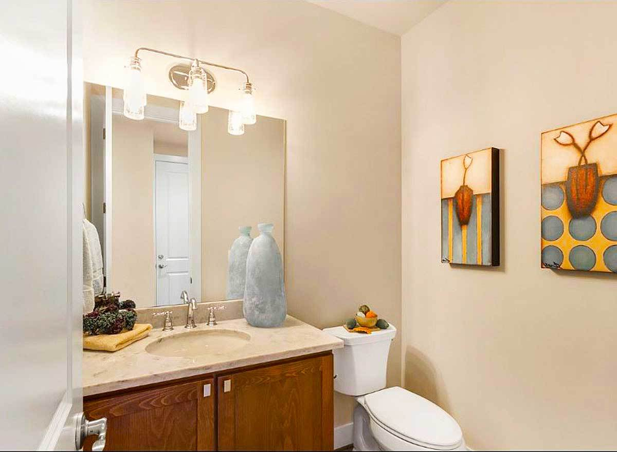 The powder room has a toilet and a sink vanity illuminated with glass sconces.