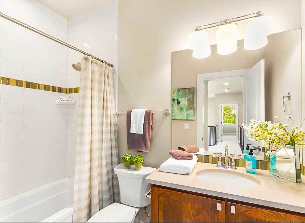 This bathroom offers a tub and shower combo, a toilet, and sink vanity.